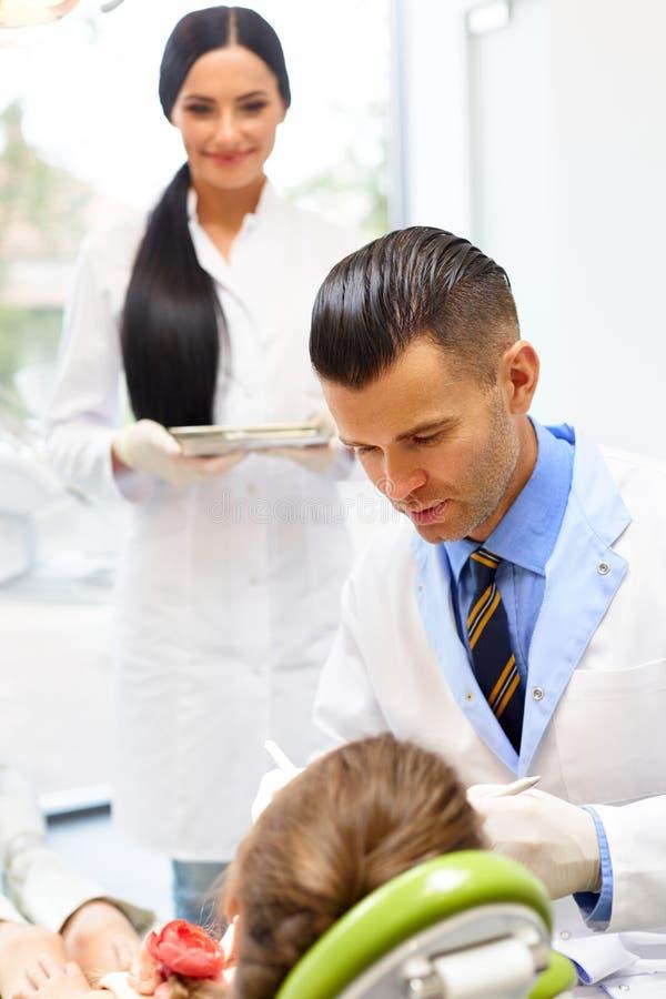 Dentiste avec l'assistant examinant des dents de petites filles dans le Denti image libre de droits