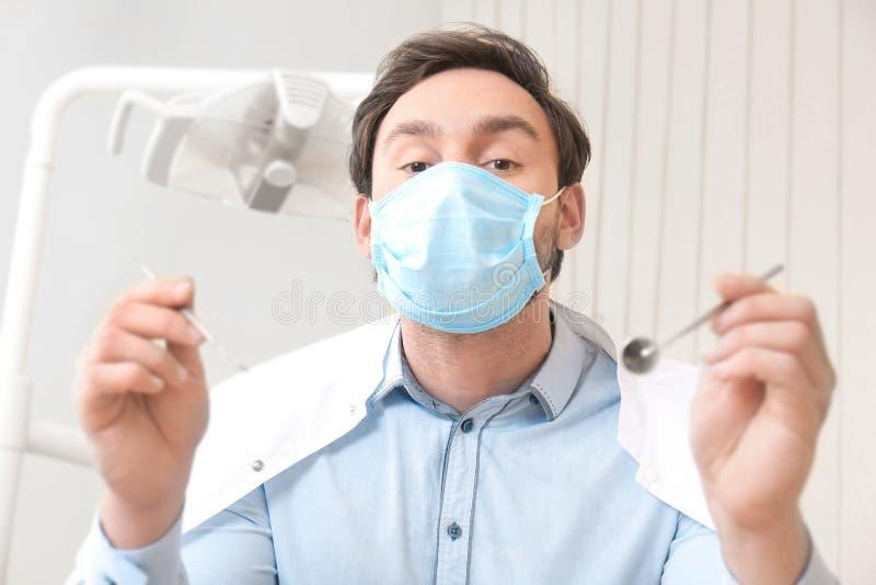 Dentiste avec le miroir et l'explorateur périodontique dans la clinique images libres de droits