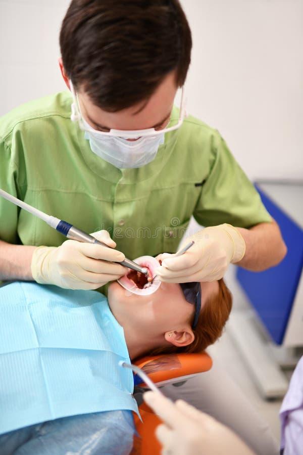 Dentiste commençant l'opération commune de nettoyer la bouche femelle images stock