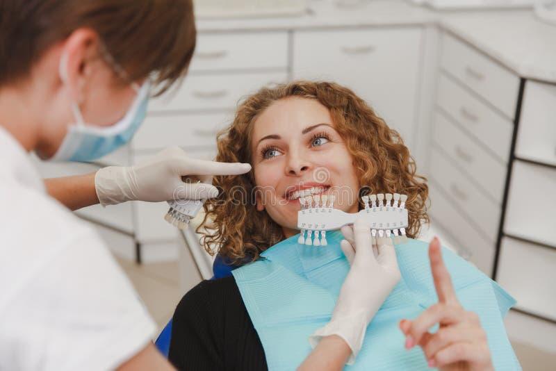 Dentiste comparant la nuance patiente de dents du ` s aux échantillons pour le traitement de blanchiment photos libres de droits