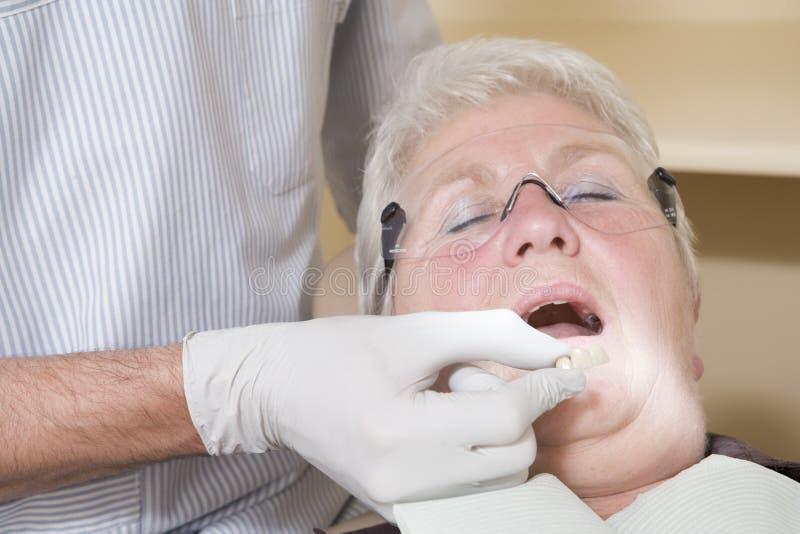 Dentiste dans des dentiers convenables de pièce d'examen sur le femme photo libre de droits