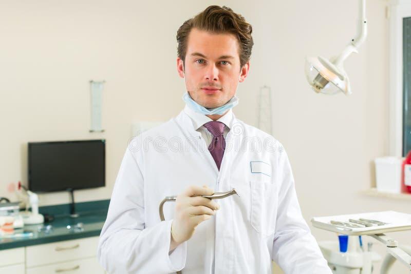 Dentiste dans sa chirurgie, il tient un foret photo stock