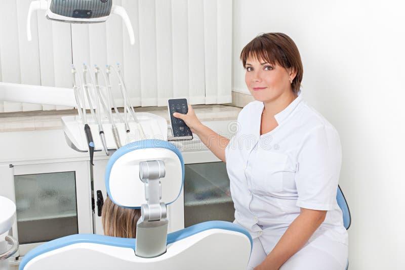 Dentiste de femme dans le bureau de dentiste photo stock
