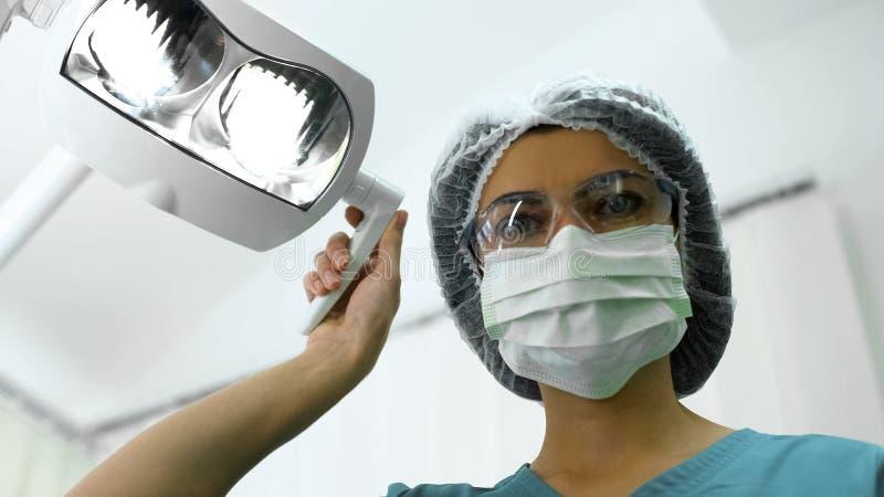 Dentiste de Madame ajustant les lumières operatory, préparation pour la chirurgie, patient POV image libre de droits