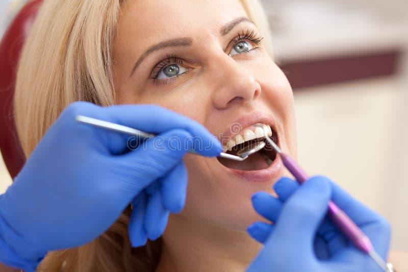 Dentiste de visite de femme mûre à la clinique images stock