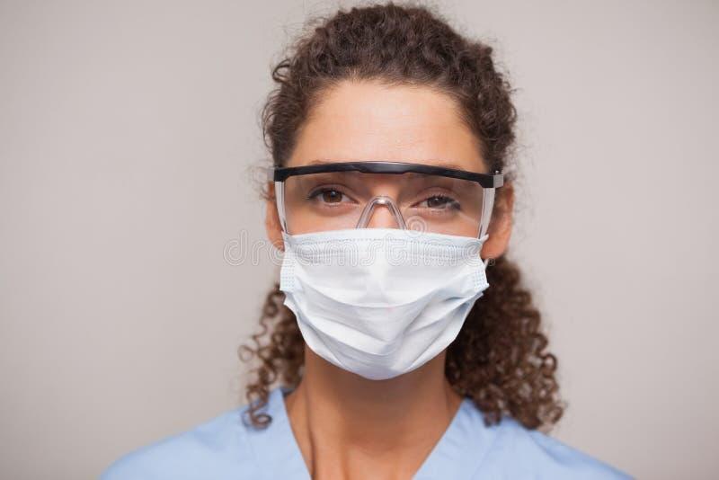 Dentiste en masque chirurgical et verres protecteurs regardant l'appareil-photo photographie stock
