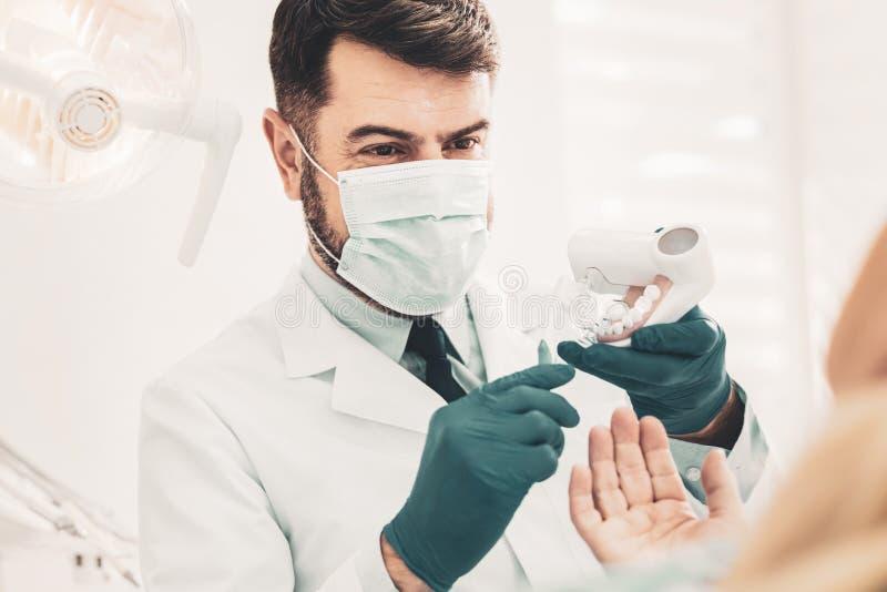 Dentiste enseignant son patient au sujet des soins dentaires photo libre de droits