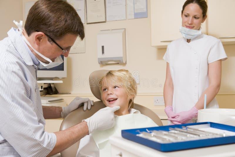 Dentiste et aide avec le jeune garçon photos libres de droits