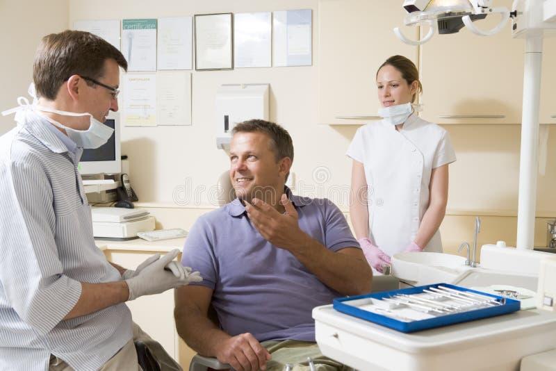 Dentiste et aide dans la chambre d'examen avec l'homme photographie stock libre de droits