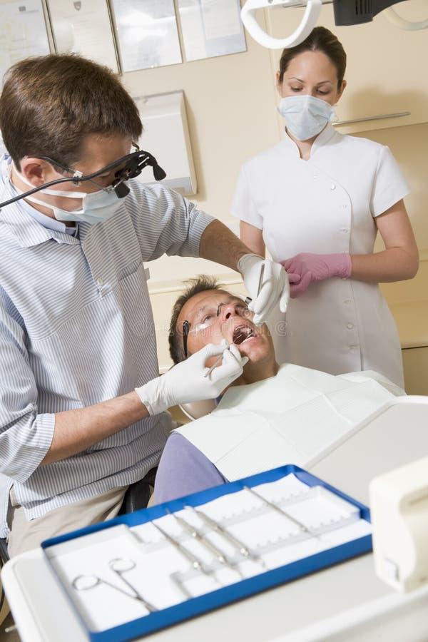 Dentiste et aide dans la chambre d'examen avec l'homme image stock