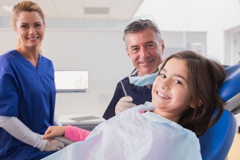 Dentiste et infirmière pédiatriques de sourire avec un jeune patient photos libres de droits