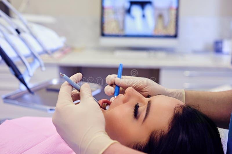 Dentiste examinant les dents femelles du ` s en art dentaire images stock