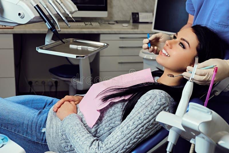 Dentiste examinant les dents femelles du ` s en art dentaire photo libre de droits