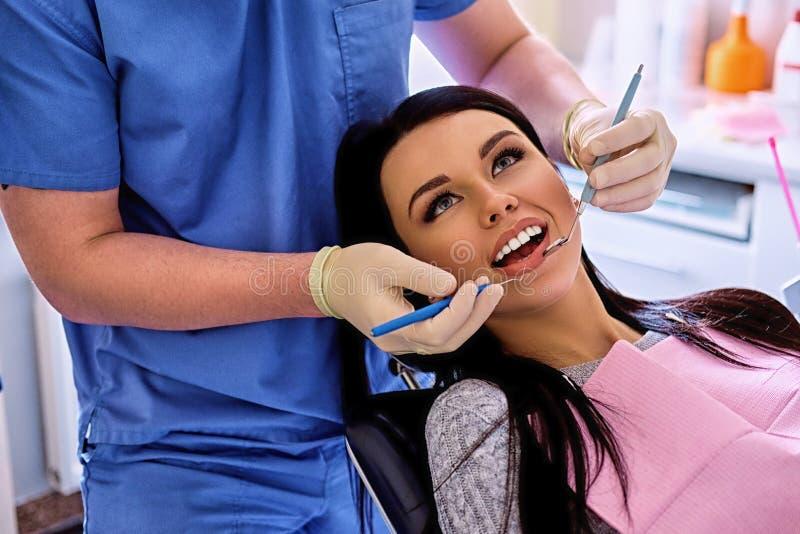 Dentiste examinant les dents femelles du ` s en art dentaire image libre de droits