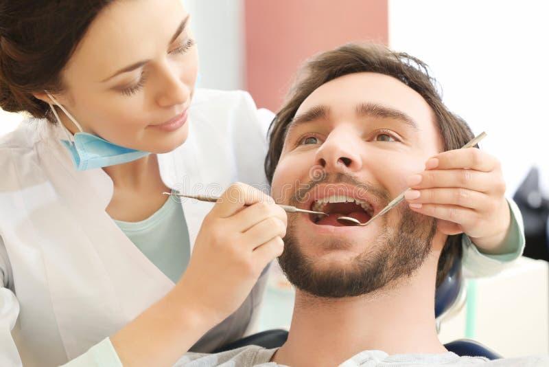 Dentiste examinant les dents patientes du ` s dans la clinique photos libres de droits
