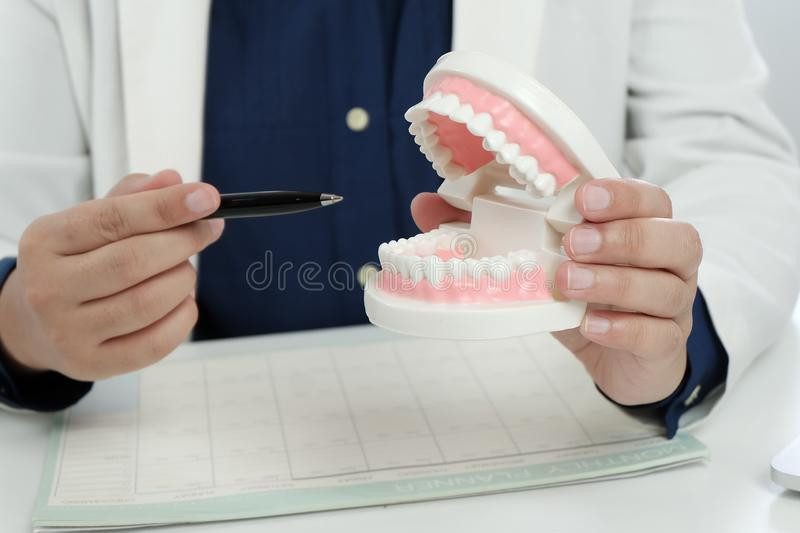 Dentiste examinant un traitement m?dical de dents patientes au bureau dentaire photo stock