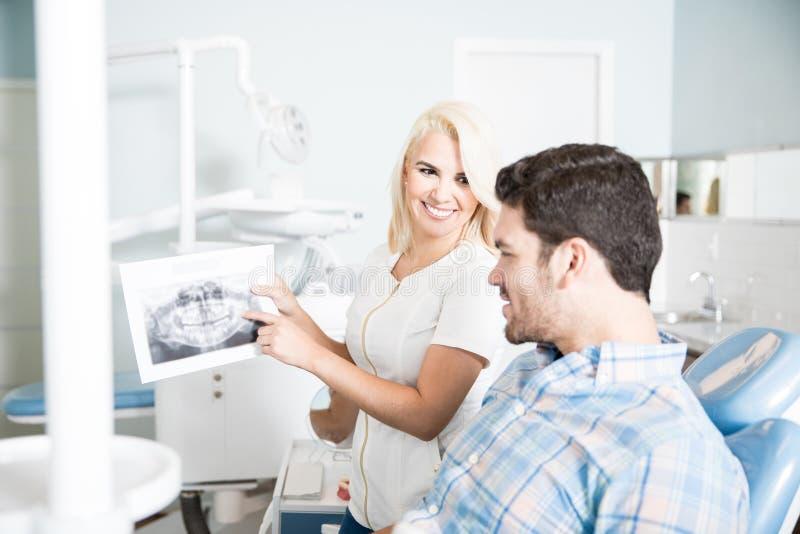 Dentiste féminin montrant des rayons X à un patient photographie stock