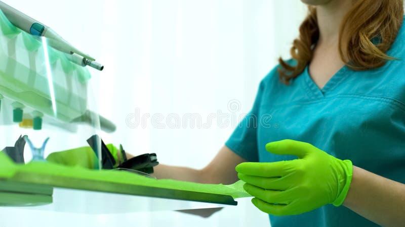 Dentiste féminin préparant l'équipement pour l'opération, gants protecteurs de port photographie stock libre de droits
