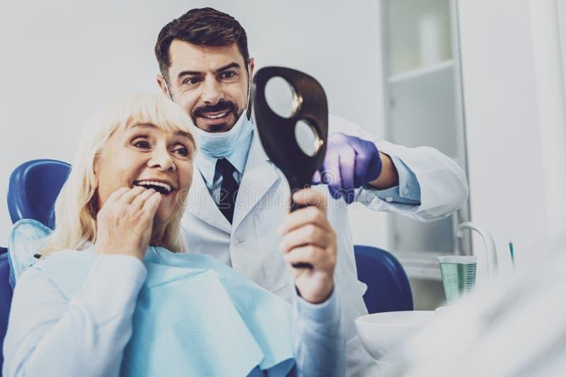 Dentiste gai se tenant près de son visiteur image libre de droits