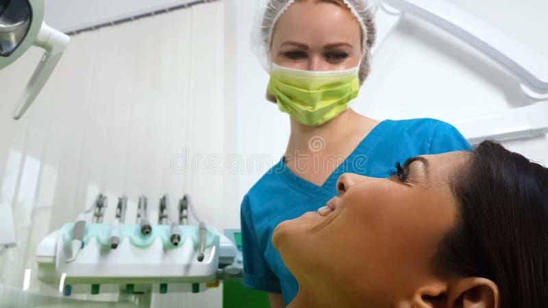 Dentiste heureux et patient souriant après opération dentaire réussie, nouvelle clinique photos libres de droits