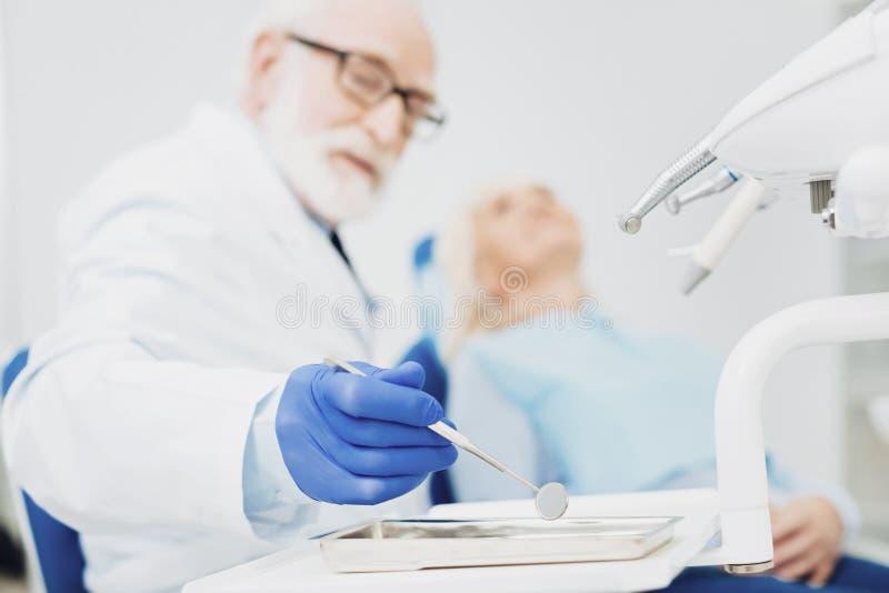 Dentiste masculin attentif obtenant le miroir dentaire photographie stock