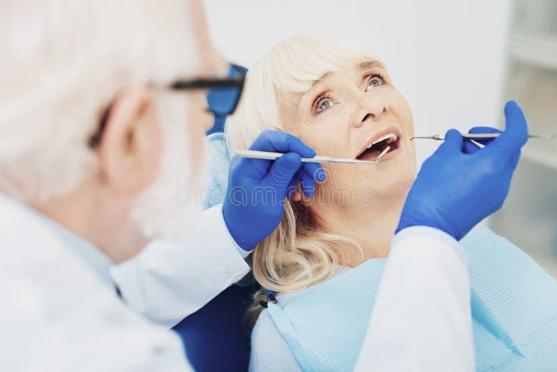 Dentiste masculin attentif vérifiant des dents de femme image libre de droits
