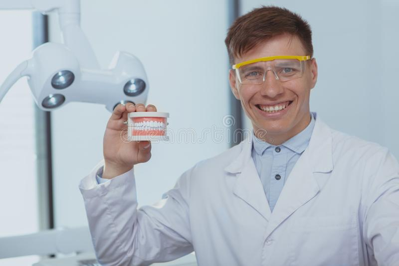 Dentiste masculin beau travaillant à sa clinique images stock