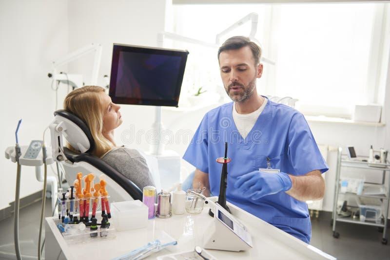 Dentiste masculin effectuant son travail dans la clinique du dentiste photo stock