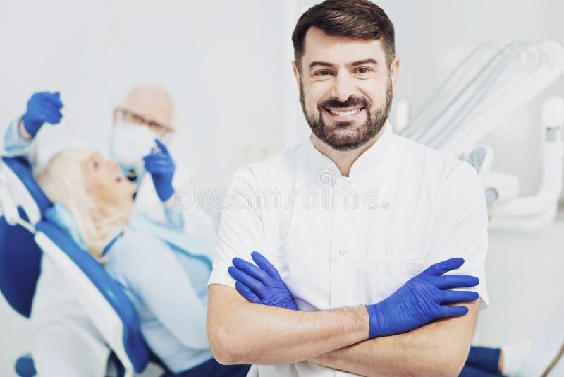 Dentiste masculin gai effectuant son travail image libre de droits