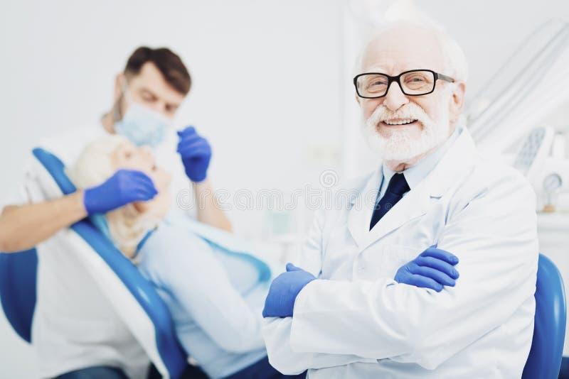 Dentiste masculin gai travaillant avec le collègue photographie stock