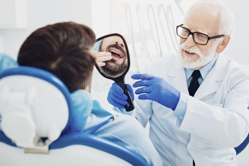 Dentiste masculin professionnel donnant le miroir au patient image libre de droits