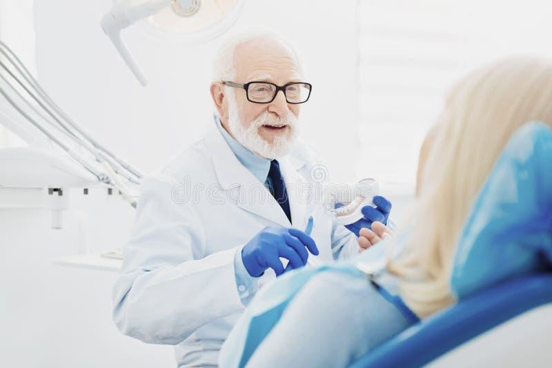 Dentiste masculin réussi expliquant le nettoyage de dents photos libres de droits