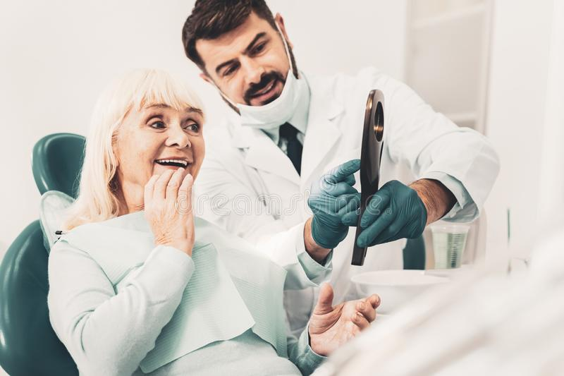 Dentiste montrant le nouveau dentier à son client photo libre de droits