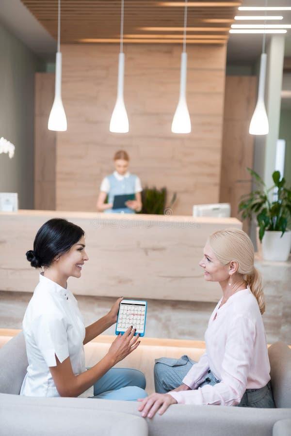 Dentiste offrant à sa patiente la date de son prochain rendez-vous photos libres de droits