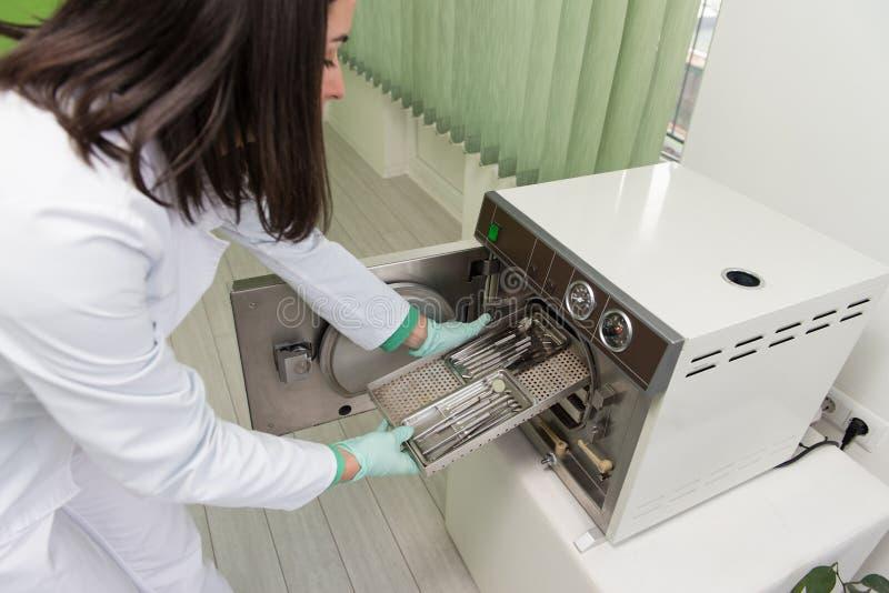 Dentiste Places Medical Autoclave pour stériliser chirurgicale photographie stock libre de droits