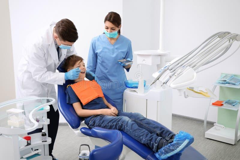 Dentiste professionnel et assistant travaillant avec peu de garçon photographie stock libre de droits
