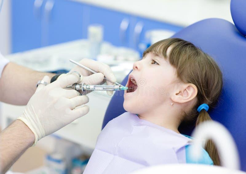 Dentiste retenant une seringue image stock