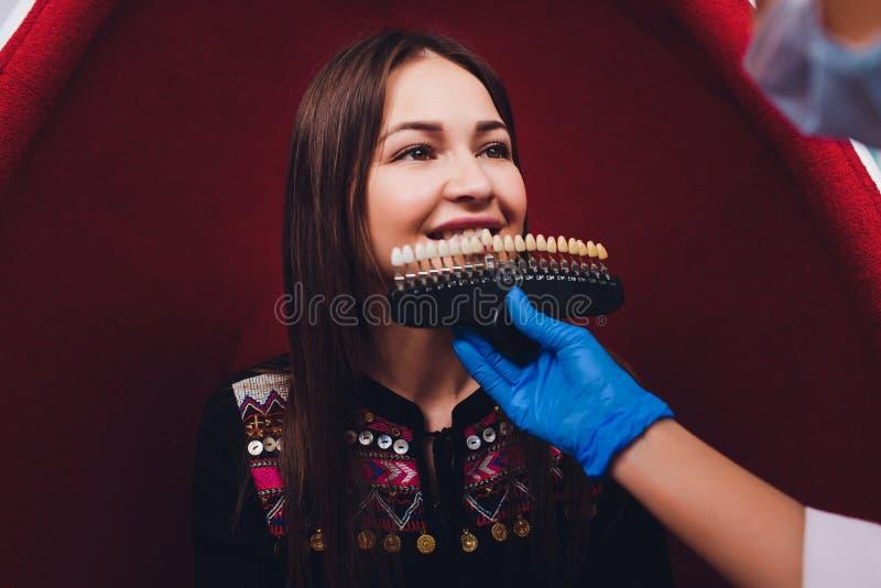 Dentiste traitant les dents patientes femelles de femme examin?es aux dents de dentistes blanchissant soin de dent de bureau de s images stock