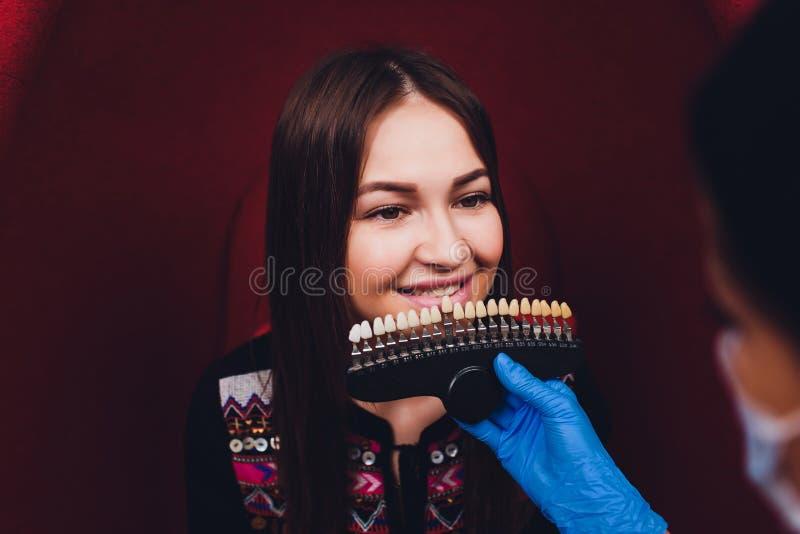 Dentiste traitant les dents patientes femelles de femme examin?es aux dents de dentistes blanchissant soin de dent de bureau de s photos libres de droits