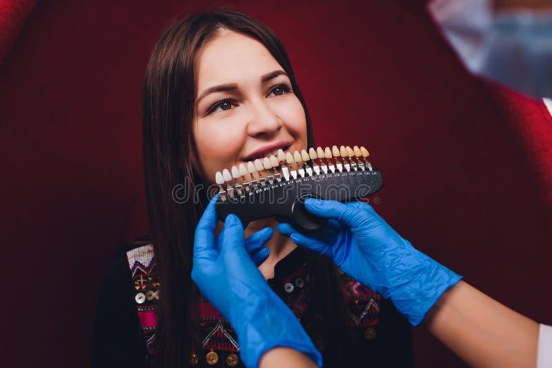 Dentiste traitant les dents patientes femelles de femme examin?es aux dents de dentistes blanchissant soin de dent de bureau de s photo libre de droits