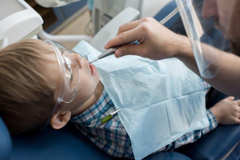 Dentiste travaillant avec l'enfant images stock