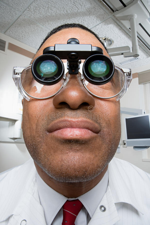Dentiste utilisant les loupes binoculaires dentaires photo stock