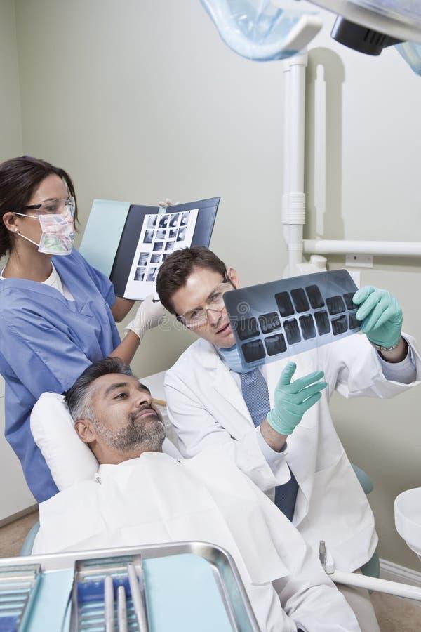 Dentisti che spiegano rapporto dei raggi x al paziente fotografie stock libere da diritti