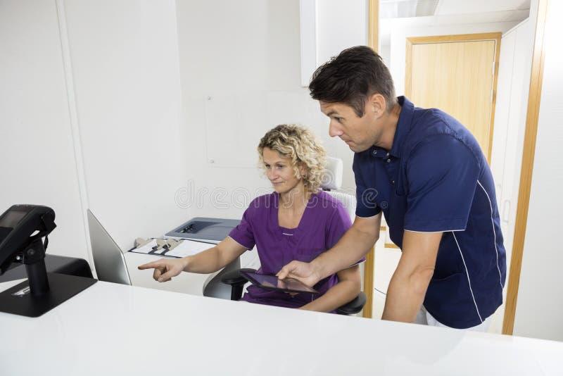 Dentisti che utilizzano computer alla reception nella clinica immagini stock libere da diritti