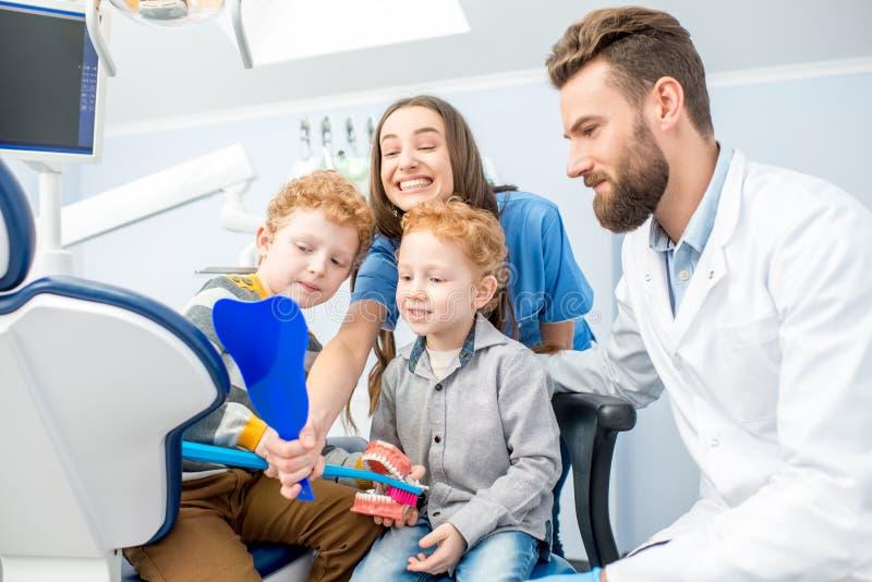Dentisti con i ragazzi al officee dentario immagini stock
