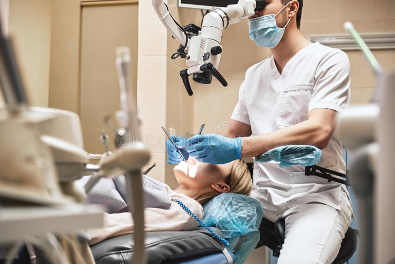Dentistry with a personal touch. Male dentist look at the patient using professional dental binocular microscope. Modern stock photography