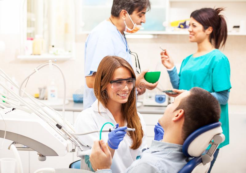 Team of  dentists examining and working on young female patient. stock image