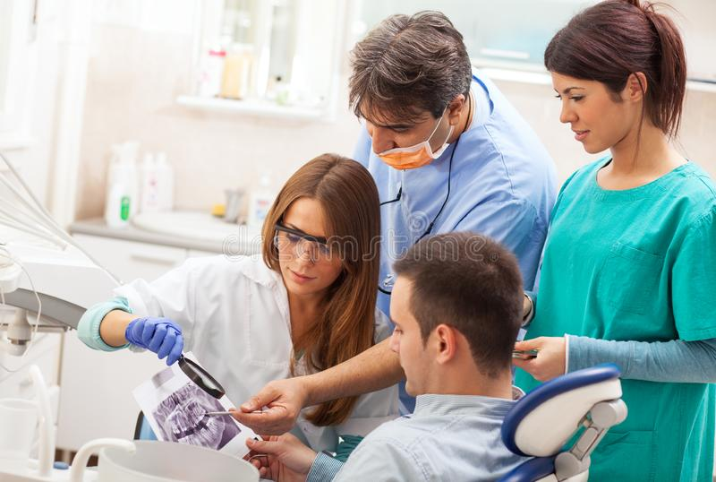 Team of  dentists examining and working on young male patient. royalty free stock photography