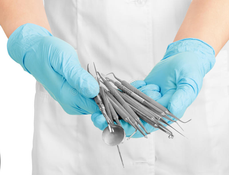 A dentists hands in blue medical gloves with dental tools stock photo