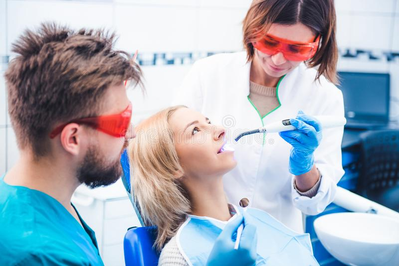 Dentists lighting dental seal with ultraviolet lamp. Dentists in red glasses lighting dental seal with ultraviolet lamp royalty free stock photo
